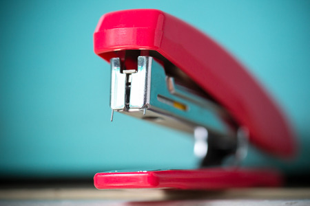 The red stapler isolated from the blue background. 版權商用圖片