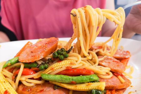 Spaghetti on a white plate is lifted up to eat