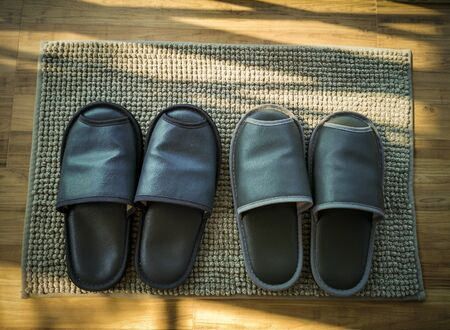 Black slippers for wearing in the room.