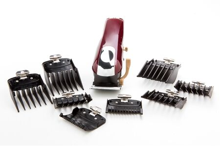 Clippers and accessories for cutting hair on a white background