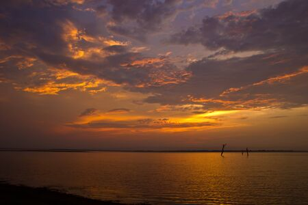 Sunset over sea with moody sky, dark storm clouds Stock Photo