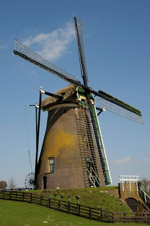 Historical windmill in typical dutch landscape
