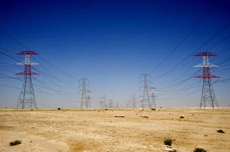 Long lines of powerline towers stretching across the Qatar desert