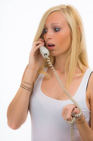 A teenage blonde girl on the telephone getting a very bad news and is worried