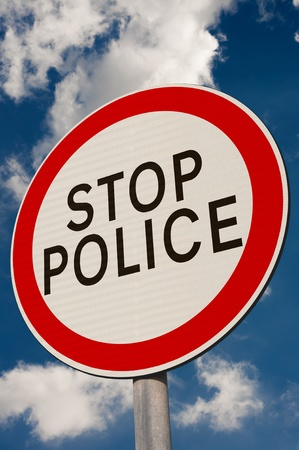 Stop Police sign against a blue sky.