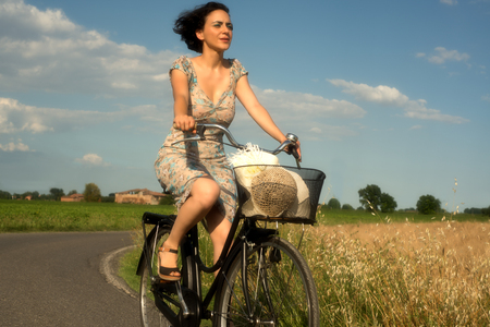 Girl on a bike in the summer countryside