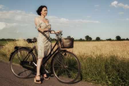 Girl on a bike in the summer countryside photo