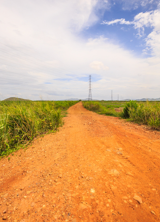 unpaved road: This red soil unpaved road leads us into the middle of nowhere. Stock Photo