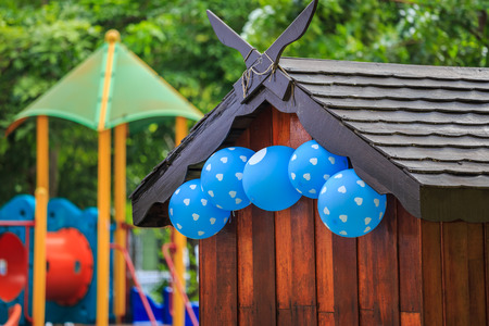 Wooden playhouse at a playpark with blue balloons photo