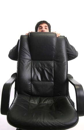 businessman hiding behind his chair photo