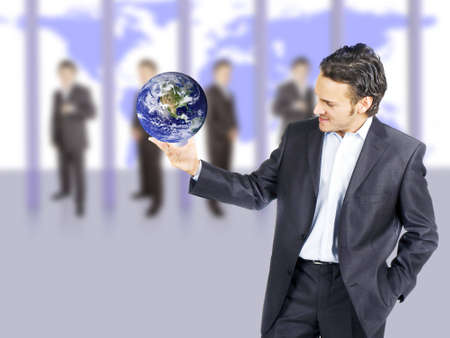 businessman is in a huge room with a world map in the background with his team photo