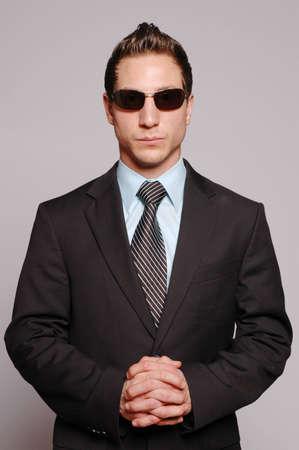 secret service: a businessman is posing against gray background