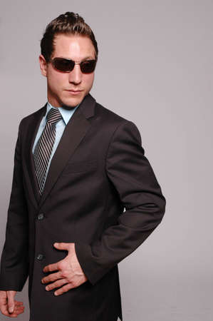 a businessman is posing against gray background