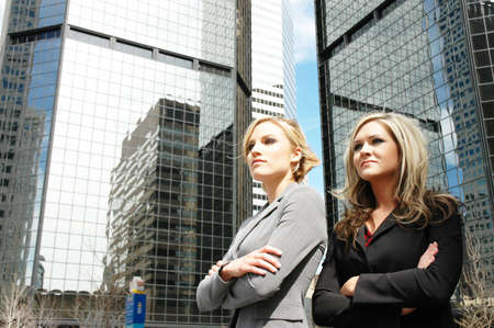 employe: business women posing in front of a skyscraper in downtown denver