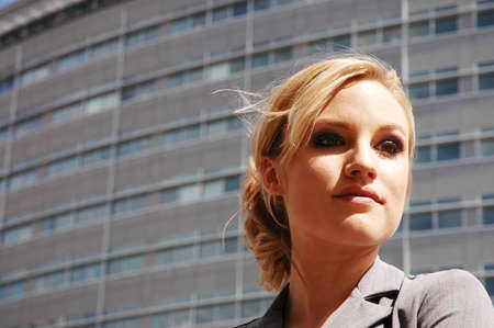 business woman is posing in front of some corporate buildings