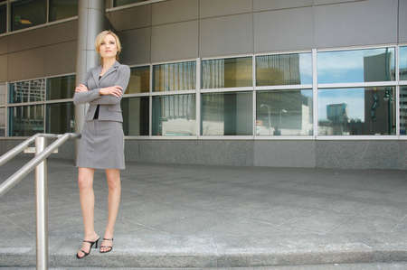 business woman is posing in front of some business buildings Фото со стока