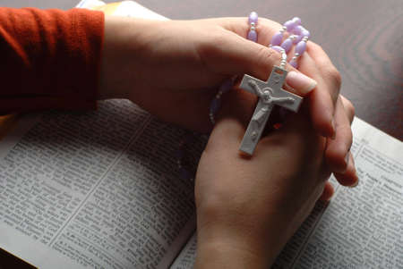 holy bible open with a cross on a hand photo