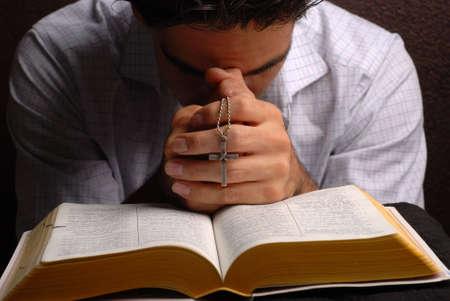 różaniec: Pismo Święte otwarte z krzyżem w dłoni