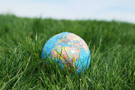 a miniture earth is placed on green grass showing europe and africa