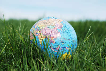 a miniture earth showing asia is placed on green grass