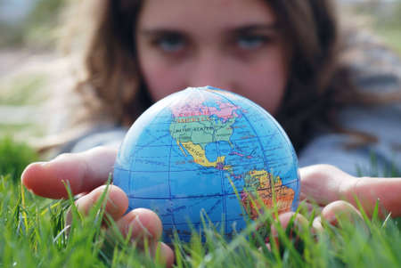 earth is being held by a little girls hands