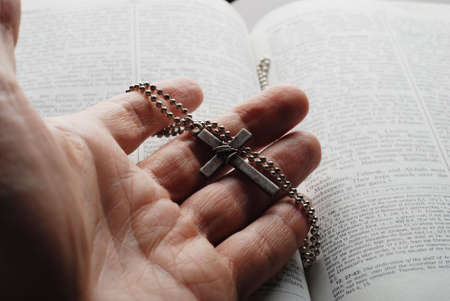 holy bible open with a cross on a hand Stock Photo - 2504358