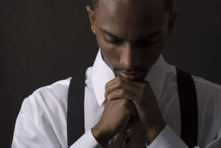 man praying: African American businessman is thinking intensely