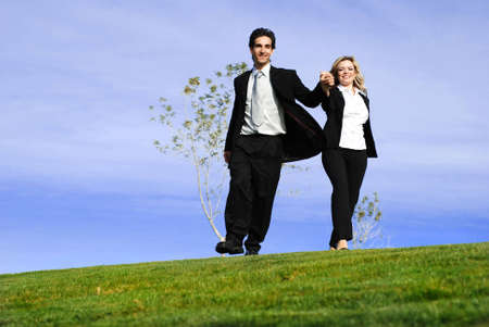 portrait of a confident and successful business partners running in the field photo