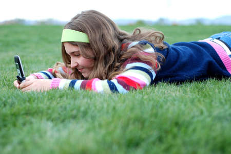 young blond girl in the park and cell phone