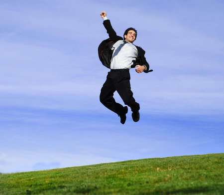 successful: successful and happy young adult businessman running and jumping in the green field