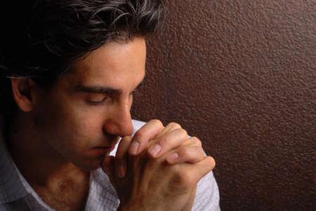 hoopt: een trieste man bidden voor zijn problemen op te lossen Stockfoto