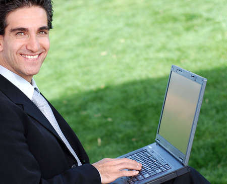 businessman working at his computer: confident and successful young adult businessman working on his laptop computer
