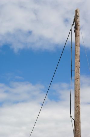 A simple wooden electricity pole against a blue, clouded sky. Stock Photo