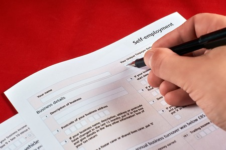 human fills self employment tax form on red velvet background