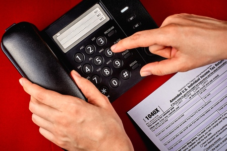 Human dials a phone number next to tax Form 1040X on a and red velvet background, close-up