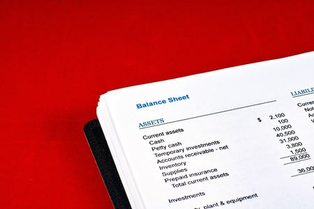 balance sheet on a and red velvet background, close-up Archivio Fotografico