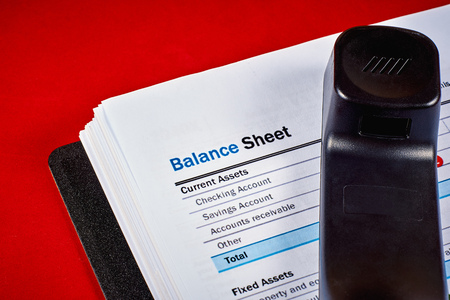 Balance sheet and tube phone on a red velvet background, close-up