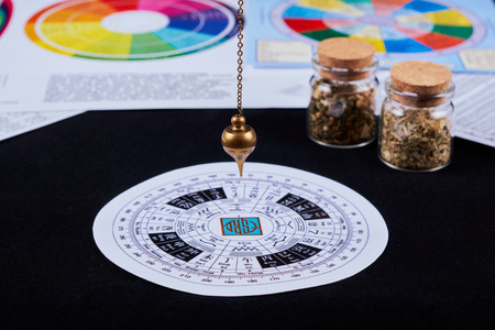 Astrological pendulum for tarot and astrological circle on the background of astrological charts, magical potions and astrological horoscopes