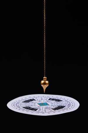 Astrological pendulum for tarot and astrological circle on the black velvet background