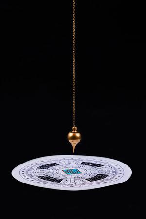Péndulo astrológico para tarot y círculo astrológico sobre el fondo de terciopelo negro Foto de archivo