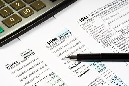 Tax Form 1040 1041 1040EZ pen and calculator, close-up