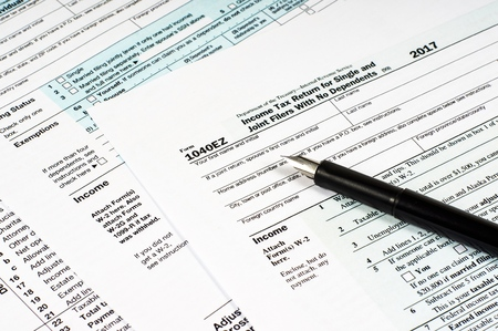 Tax Form 1040EZ and pen on different form background. close-up