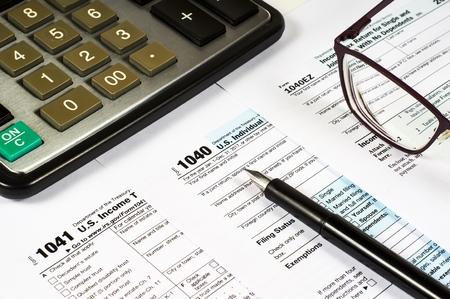 Formulaire fiscal 1040, 1041, 1040EZ et stylo sur fond de calculatrice et lunettes, gros plan