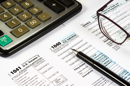Formulario de impuestos 1040, 1041, 1040EZ y lápiz sobre un fondo de una calculadora y gafas, close-up