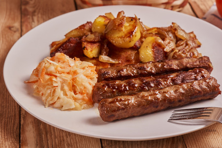 Serbian cevapi, cevapcici, Balkan minced meat kebab on a white plate with marinated cabbage, fried potatoes and fried onions next to fork on a wooden background