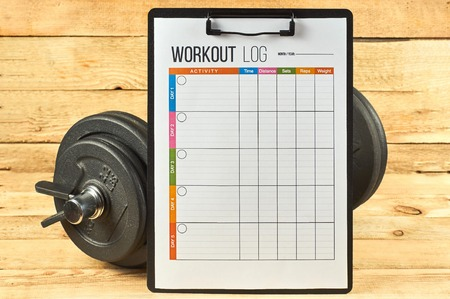 Healthy lifestyle concept. Mock up on workout and fitness dieting diary. Workout log sheet and dumbbell on a wooden background. Stock fotó