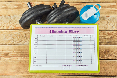 Healthy lifestyle concept. Mock up on workout and fitness dieting diary. Slimming diary sheet, blue shaker and dumbbells on a rustic wooden background