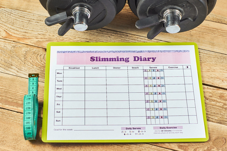 Healthy lifestyle concept. Mock up on workout and fitness dieting diary. Slimming diary sheet, measuring tape and dumbbells on a rustic wooden table