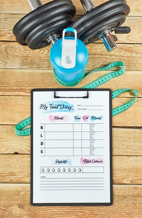 Healthy lifestyle concept. Mock up on workout and fitness dieting diary with copy space. Food diary sheet, measuring tape, blue shaker and dumbbells on a rustic wooden background