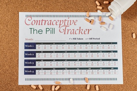 Contraceptive tracker sheet and pills on corkwood background, flat lay Stock fotó